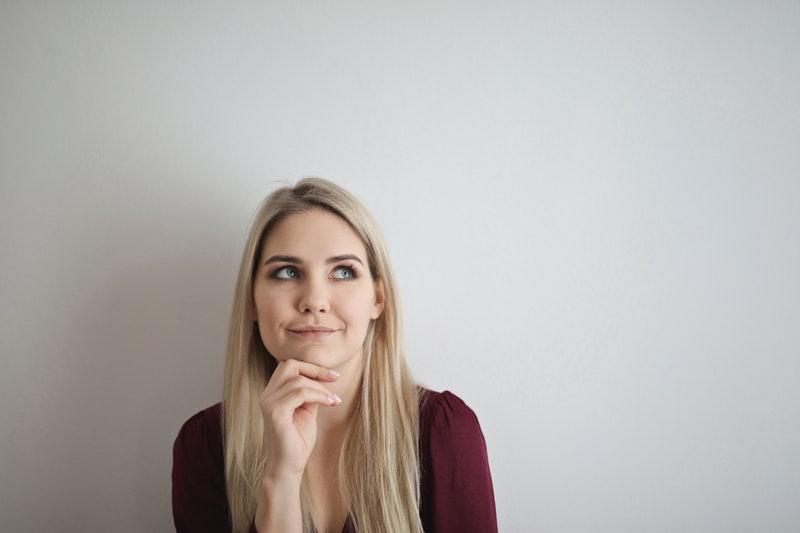 Frau überlegt vor grauem Hintergrund, ob sie sich gesetzlich oder privat versichern soll.