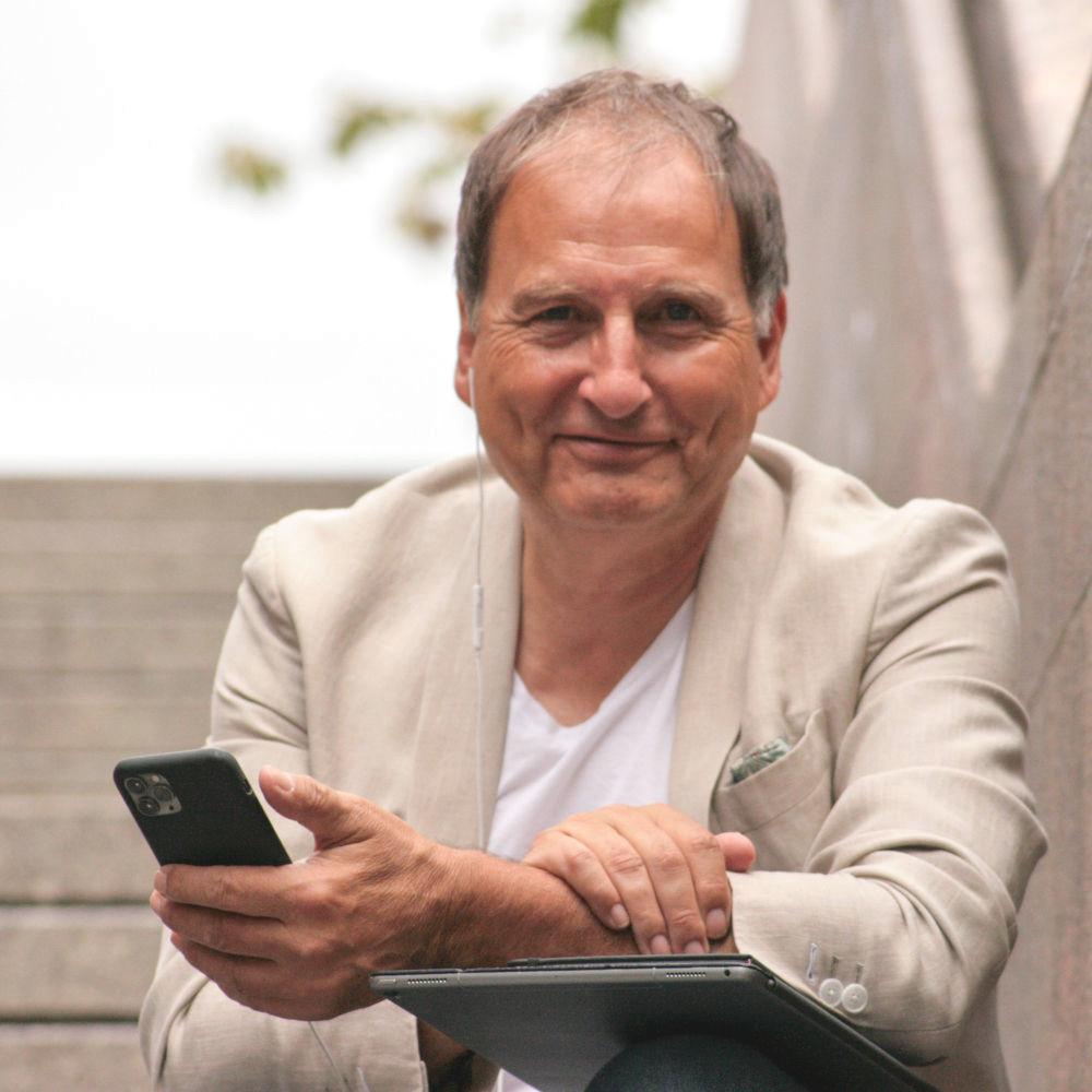 Versicherungsberater Gerd Güssler sitzt mit seinem Tablet und Smartphone auf einer Treppe und lächelt in die Kamera