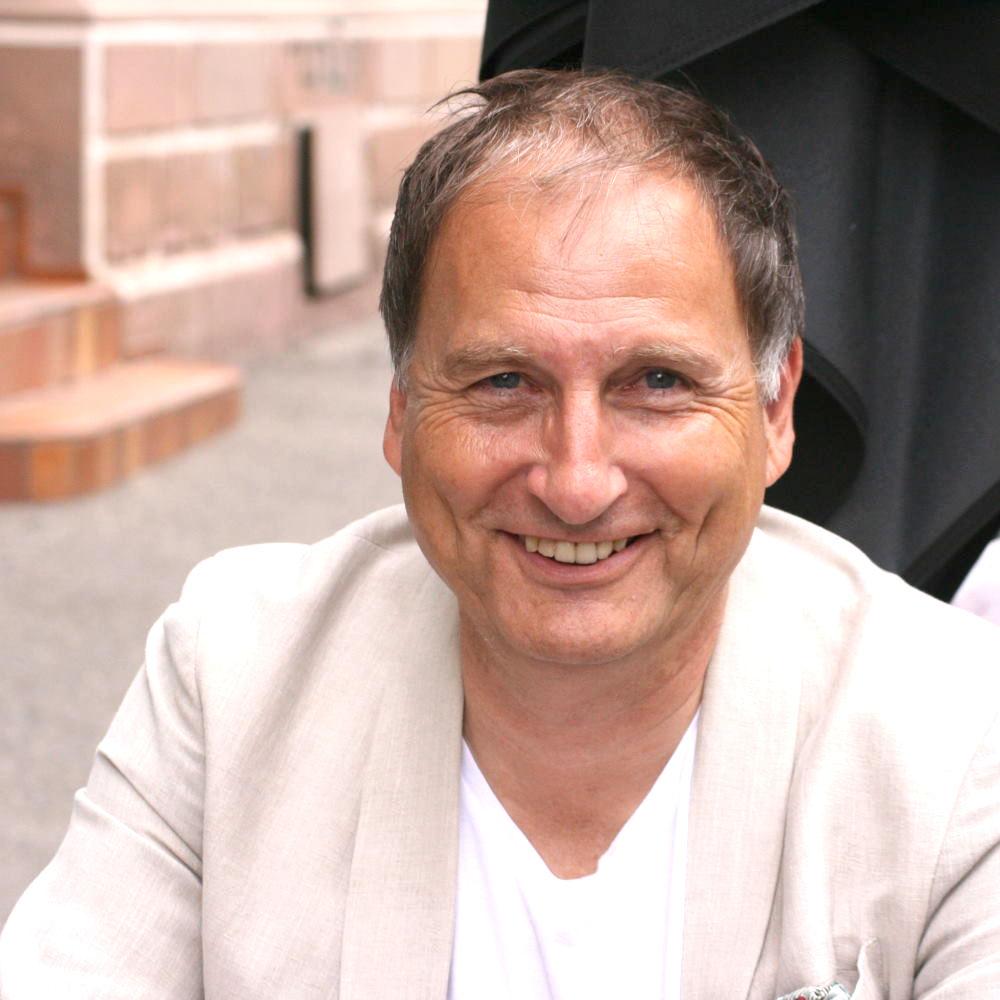 Der unabhängige Versicherungsberater Gerd Güssler lächelt im beigen Sacko in die Kamera.
