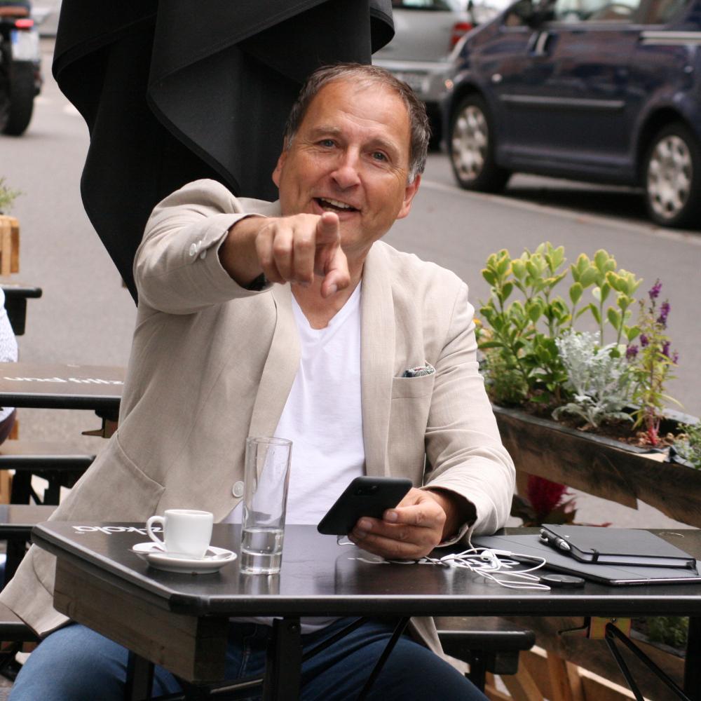 Versicherungsberater Gerd Güssler sitzt am Tisch und zeigt auf die Kamera.