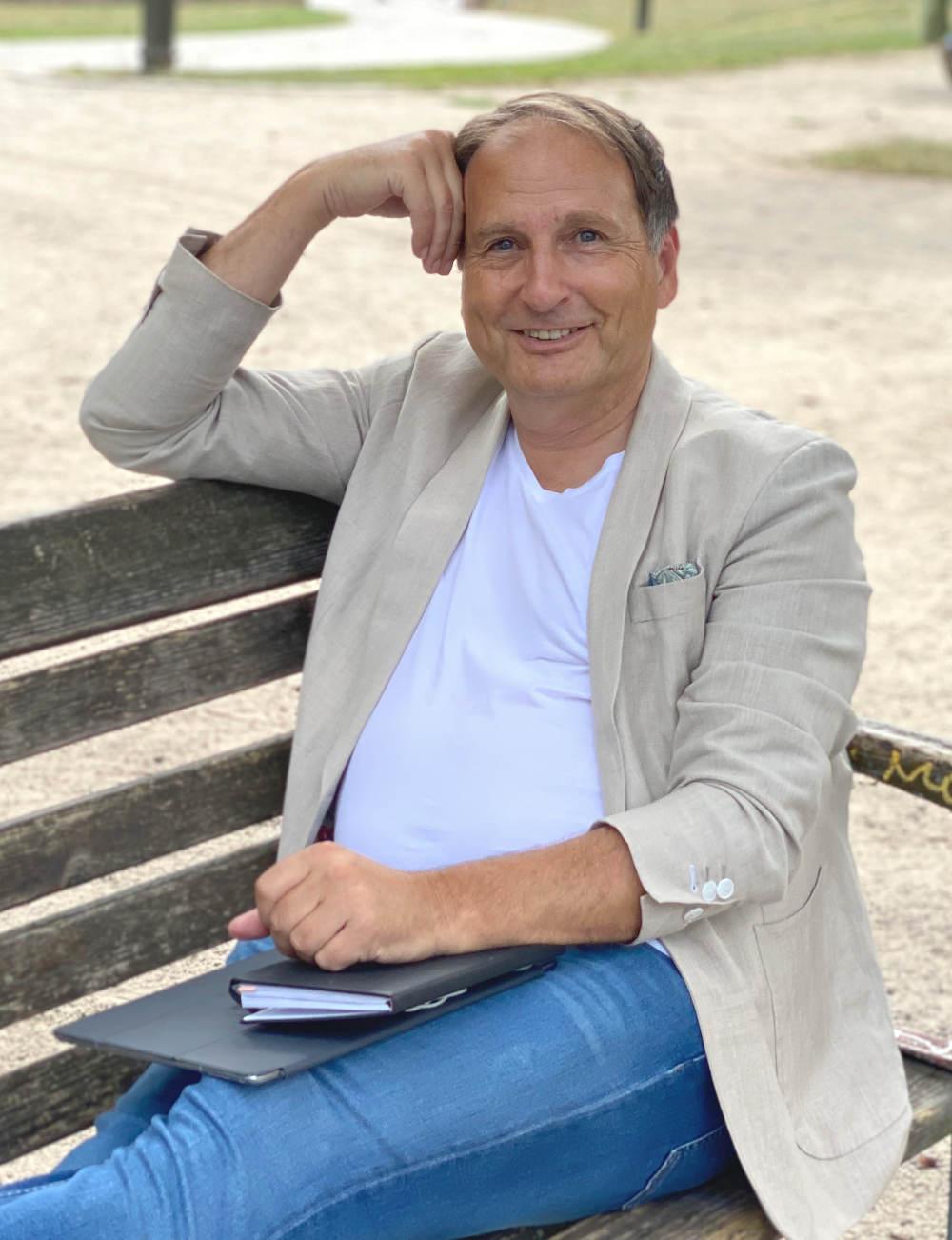 Versicherungsberater Gerd Güssler sitzt lächelnd auf einer Parkbank