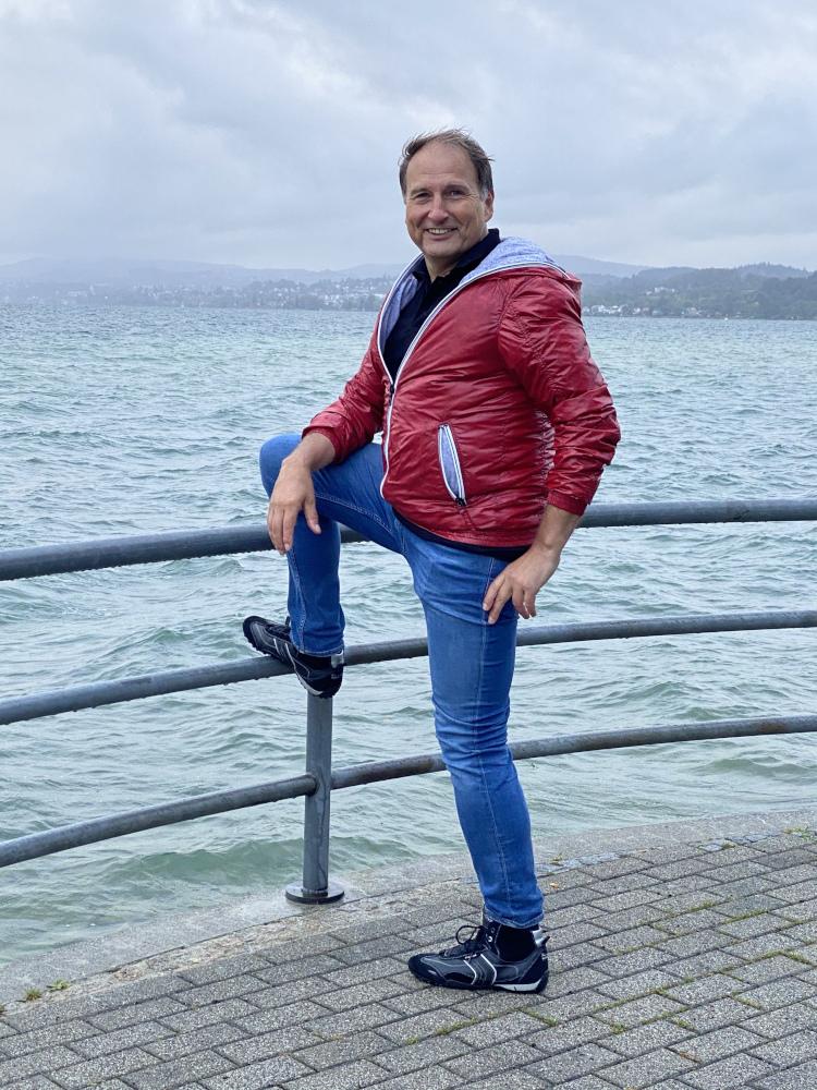 Versicherungsberater Gerd Güssler steht in legerer Kleidung am Meer und freut sich, dir seine Selbstlern-Lösung vorzustellen.