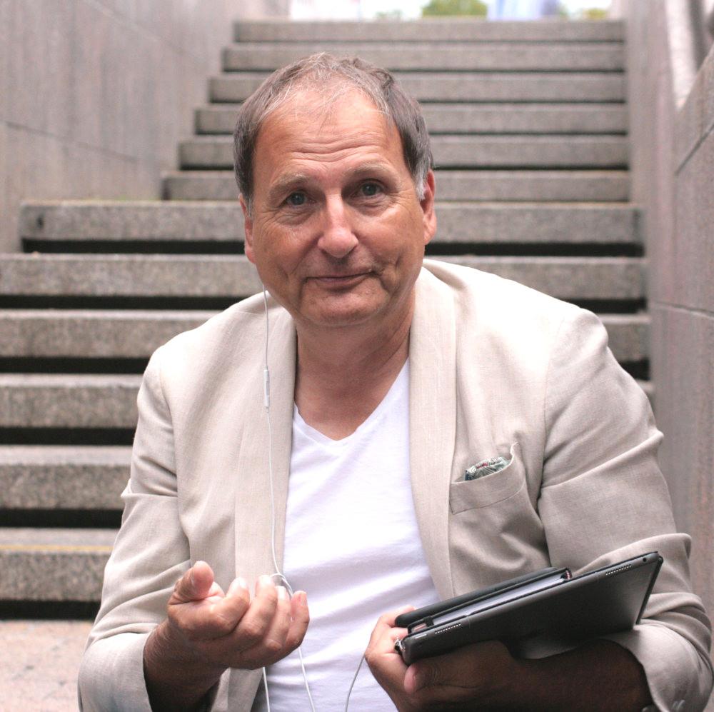 Versicherungsberater Gerd Güssler sitzt auf einer Treppe und hält sein Tablet in der Hand. Er blickt in die Kamera und würde sich freuen, dich in Sachen Versicherung zu beraten.