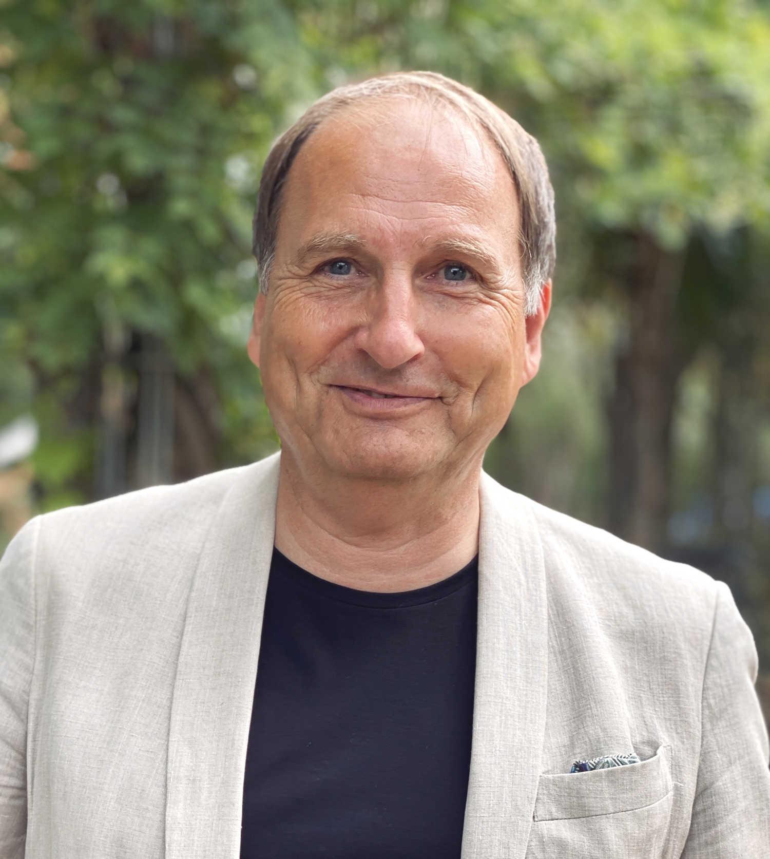 Der unabhängige Versicherungsberater Gerd Güssler steht vor einem grünen Hintergrund und ist für alle Fragen zur privaten Krankenversicherung bereit.