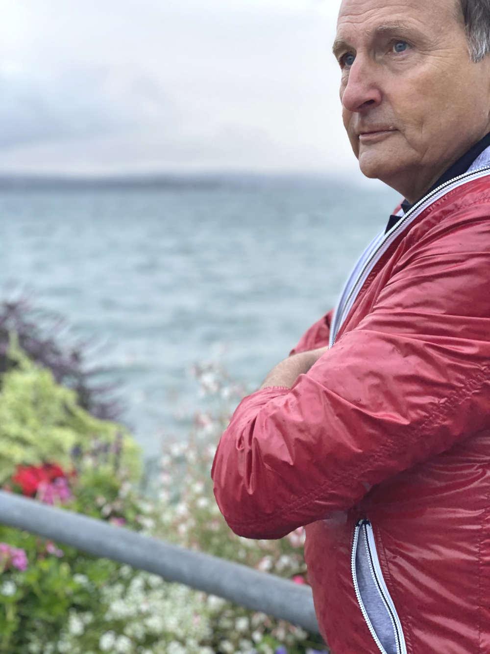 Versicherungsberater Gerd Güssler steht in einer roten Jacke am Wasser und denkt darüber nach, wie er dir mit seiner Versicherungsberatung weiterhelfen kann