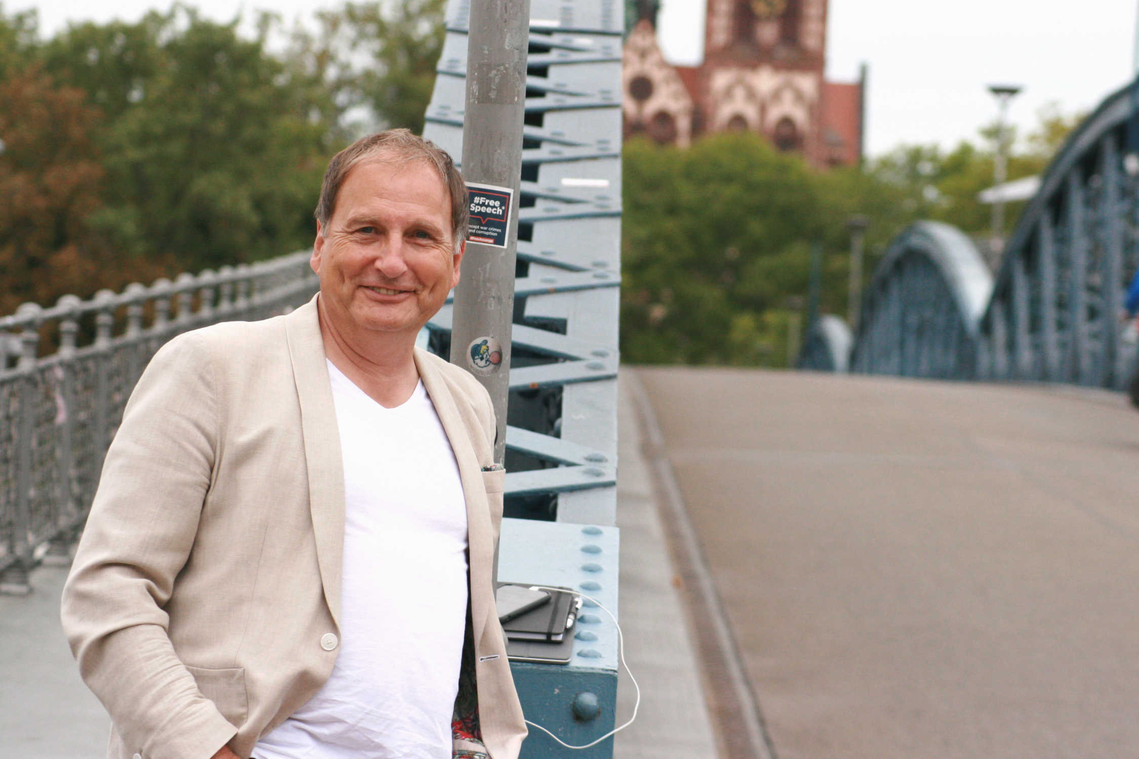 Versicherungsberater Gerd Güssler steht auf einer Brücke und lächelt.