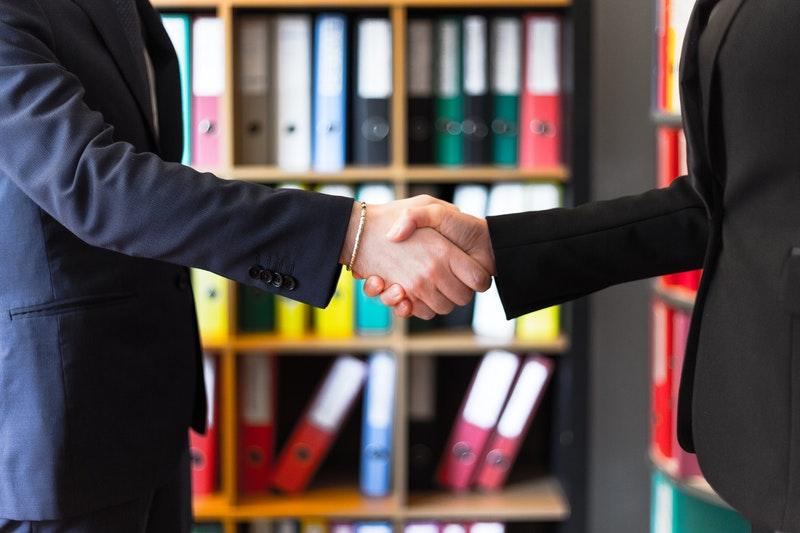Versicherungsvermittler und sein Kunde schütteln die Hände nach einem erfolgreichen Vertragsabschluss. Foto: Oleg Magni, Pexels