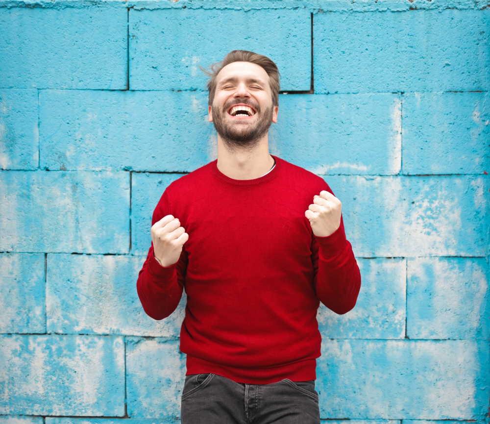 Mann im roten Pulli freut sich vor einer blauen Wand über die vielen Vorteile der privaten Krankenversicherung. Foto: bruce mars, Unsplash