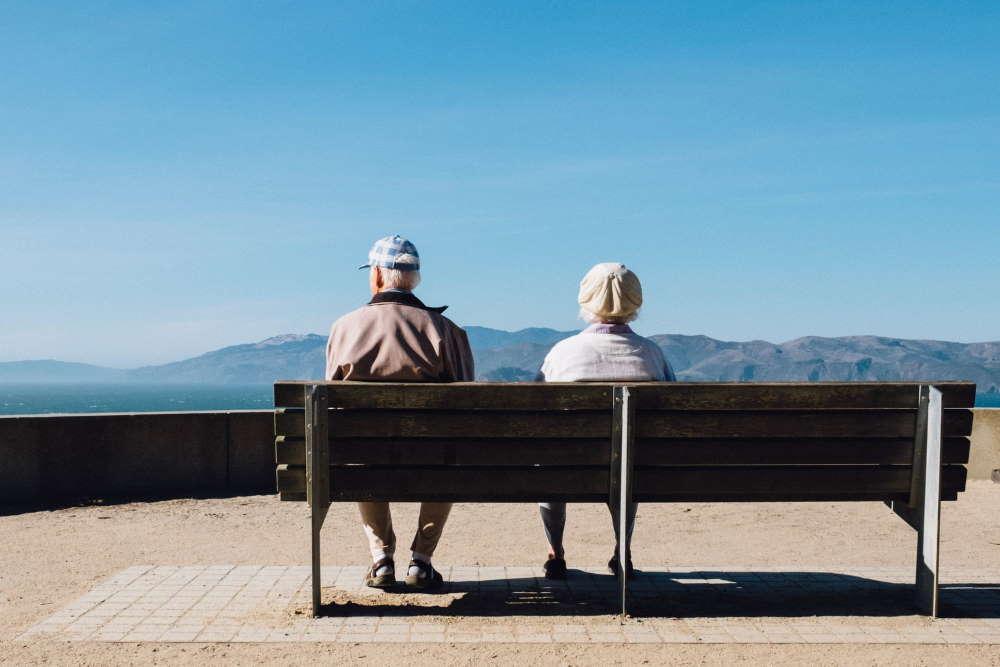 Ein Seniorenpaar sitzt in den Bergen auf einer Bank und genießt ihren Ruhestand mit bezahlbaren Beiträgen der privaten Krankenversicherung. Foto: Matthew Bennett, Unsplash