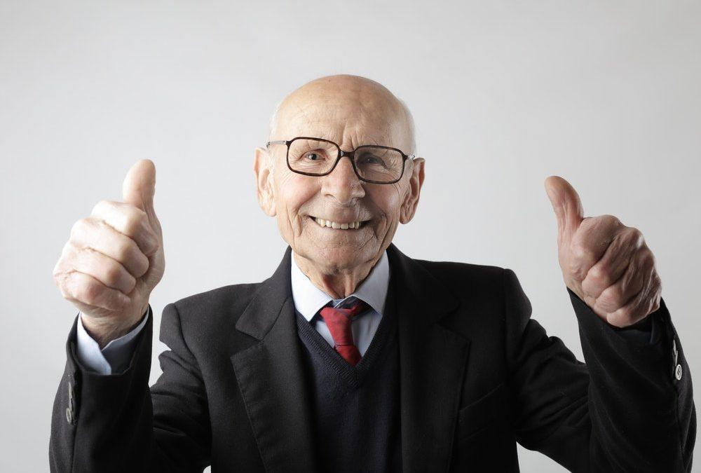 Ein älterer Herr im Anzug zeigt die Daumen hoch, denn er ist mit seiner privaten Krankenversicherung und den monatlichen Beiträgen glücklich und zufrieden. Foto: Andrea Piacquadio, Pexels