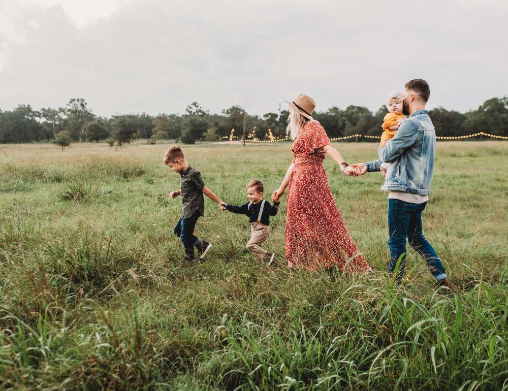 Eine Familie spaziert, zufrieden mit ihrer Krankenversicherung, über ein Feld