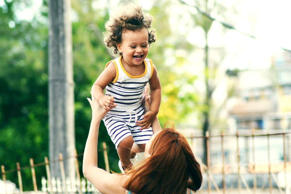 Frau wirft, glücklich über ihre Absicherung, ihr lachendes Kind in die Luft