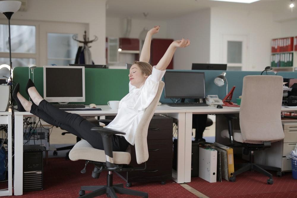 Eine Arbeitnehmerin lehnt sich im Büro mit den Füßen auf dem Tisch entspannt zurück, da sie weiß, dass sie mit der besten privaten Krankenversicherung für Angestellte optimal abgesichert ist. Foto: Andrea Piacquadio, Pexels