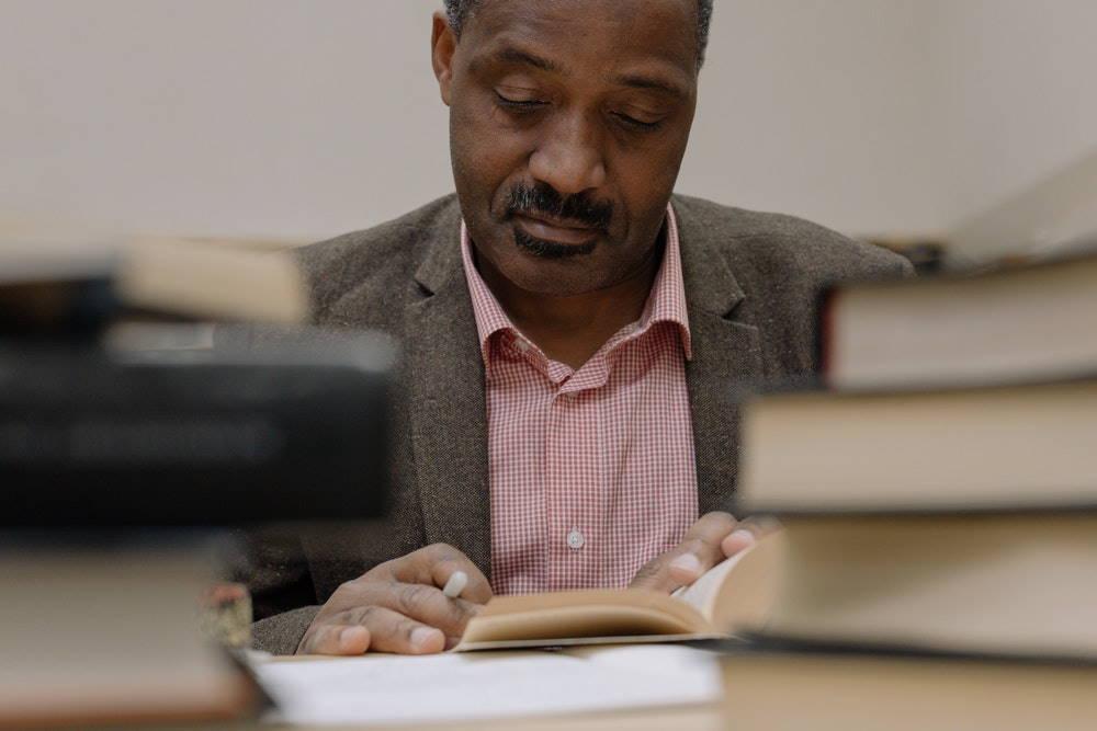 Ein Beamter sitzt zwischen seinen Büchern und widmet sich konzentriert seiner Arbeit, denn er weiß, dass er mit dem passenden Versicherungsschutz optimal abgesichert ist. Foto: cottonbro, Pexels
