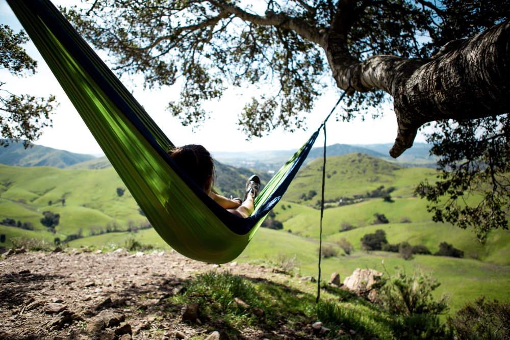 Eine Frau liegt entspannt in einer Hängematte über einer grünen Landschaft