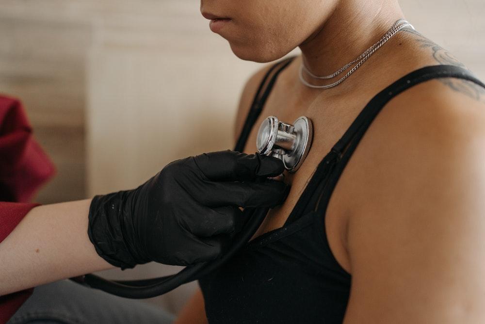Eine Frau wird von einer Ärztin abgehört, um den Gesundheitszustand für die private Krankenversicherung zu ermitteln.