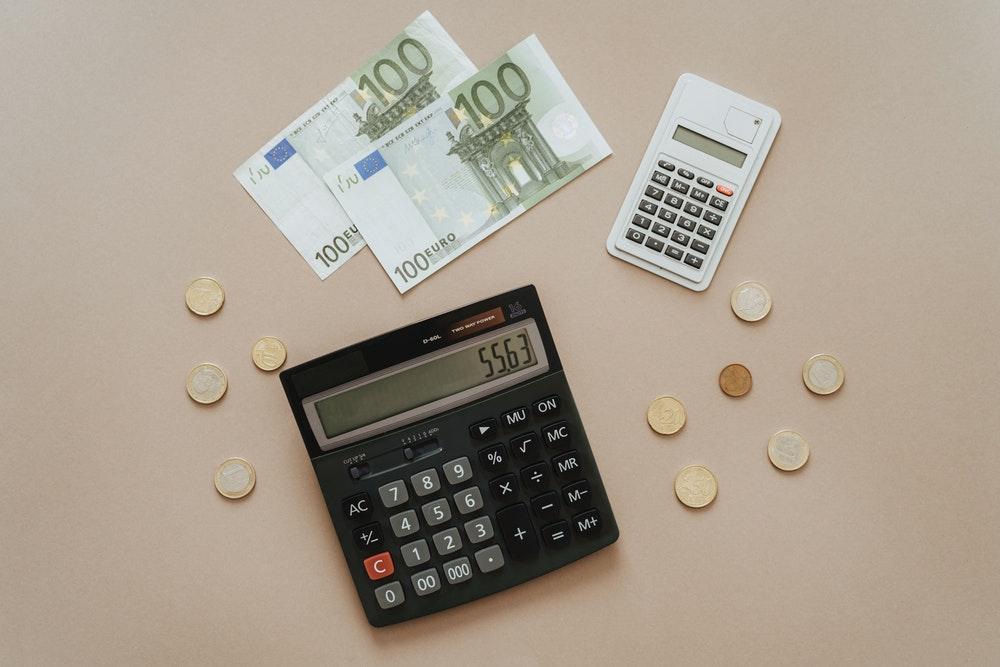 Taschenrechner mit Münzen für die Berechnung des Beitrags der privaten Krankenversicherung