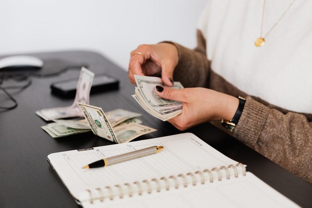 Frau zählt Geld und rechnet eine bestmögliche Selbstbeteiligung aus